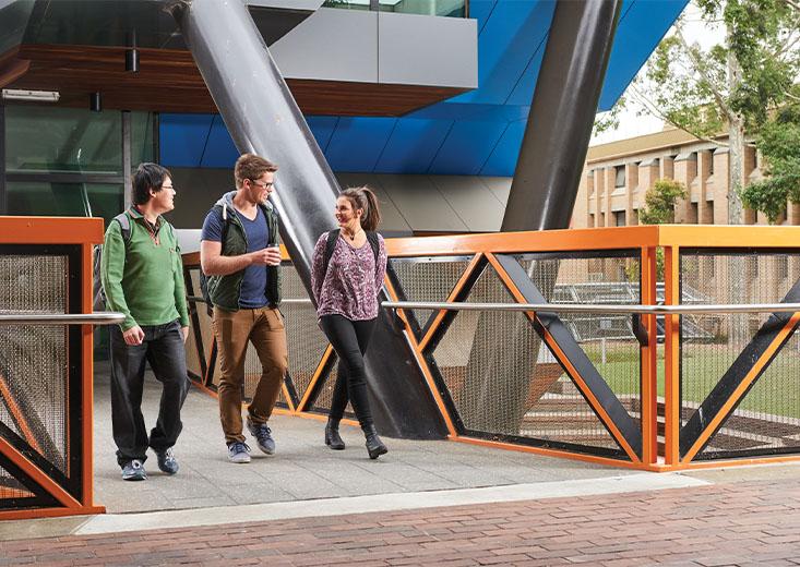 Three La Trobe University students walking out of a building.