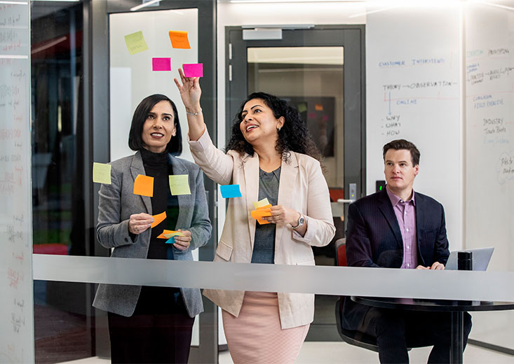 Three online MBA students using colorful sticky notes in a conference room.