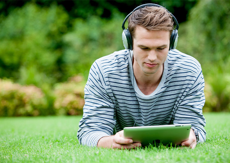 Online La Trobe student studying on a tablet laying in the grass.
